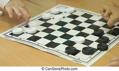 Intellectual games in kindergarten indoors. Little unidentified boy plays checkers. Close-up