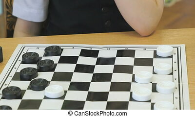 Intellectual games in kindergarten indoors. Little unidentified boy in formal attire plays checkers. Close-up