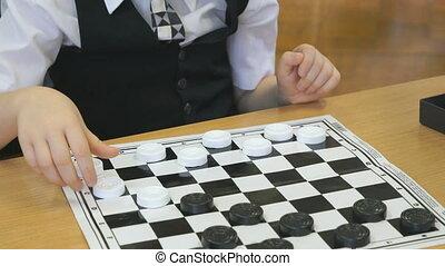 The child plays checkers in kindergarten indoors -...