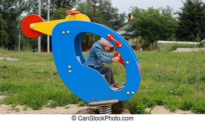 The child plays in the playground ride an attraction...