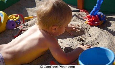 the child plays lying in the sandbox