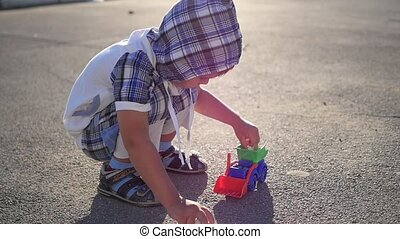 The child plays with a toy car and chalk on the playground. Outdoor games