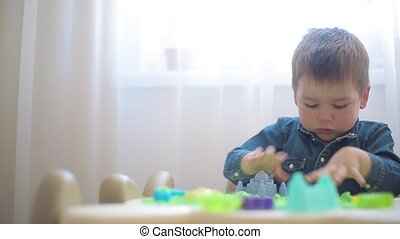 The child plays with kinetic sand and develops motor skills