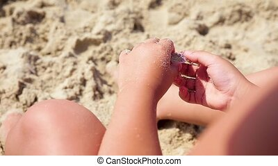 The child plays with sand on summer beach.