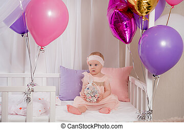 the child plays with the gift of a balloon while sitting in bed on your first birthday