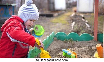 the child plays with the toys in the sandbox.Summer Sunny day. Fun and games outdoors