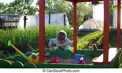 the child plays with the toys in the sandbox.Summer Sunny day