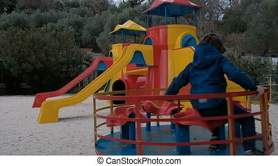 The child quickly spin on the carousel in the playground in the spring