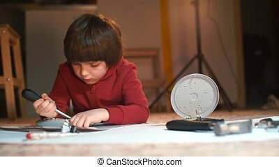 The child repairs electrical equipment lying on the floor at...