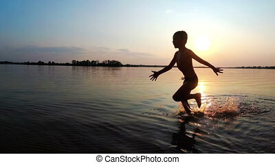 The Child Runs Along the Beach at Sunset. Slow Motion