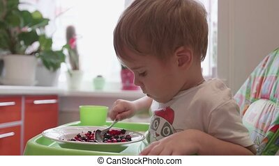 The child sits at the table and eats a spoonful of fresh...