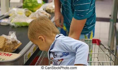 the child sits in the shopping cart in the store