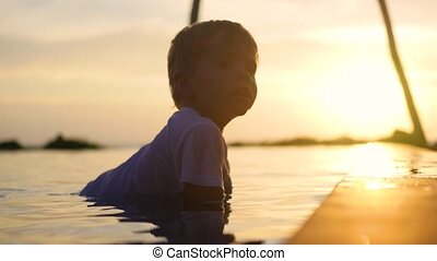 The child sits in the water and plays with a spray of water. Sunset time