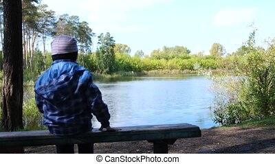 The child sits on a bench near the lake in the Park. Walks in the fresh air