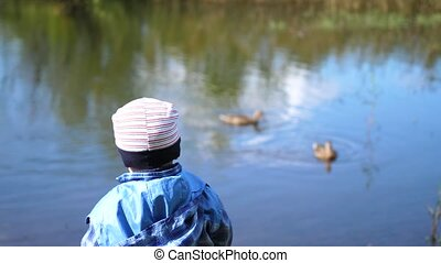 The child sits on a bench near the lake in the Park. Wild ducks swim on the lake. A beautiful scenic place. Walks in the fresh air