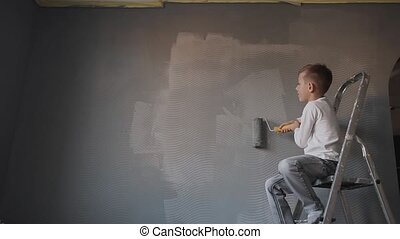 The child sits on the ladder in the room and draws the wall with a roller a gray color . The guy whitewash the wall in a new room. Happy boy paint the room
