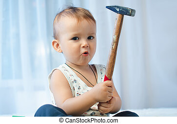 The child sits with a hammer