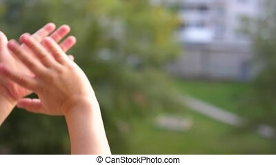 The child stands at the window and waving his hands. Close-up of hand