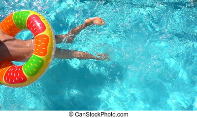 The child swims in the pool with an inflatable circle, slow motion