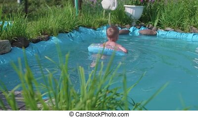 The child swims on an inflatable circle in a small pond. Garden area, flowers and plants around the lake. Happy childhood