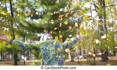the child throws up over a yellow leaves in the park