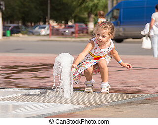 The child touched his hand to the jet fountain gushing from the earth