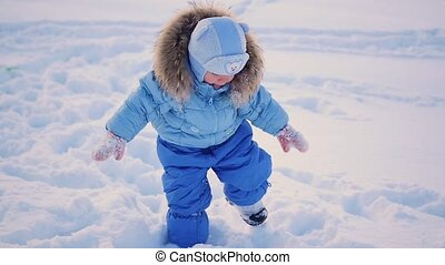 the child walks in deep snow drifts in the park