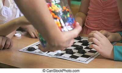Intellectual games in kindergarten indoors. Close-up of hands of little unidentified girls playing checkers
