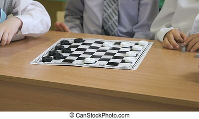 The children play checkers in kindergarten indoors -...