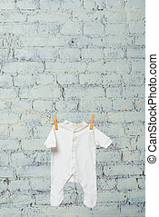 The child's white bodik dries on a rope against a white brick wall.