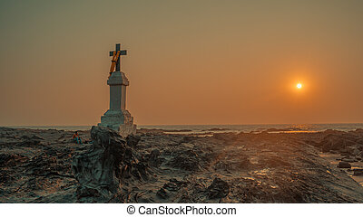 The Christian cross on the rocks by the sea against the sunset.