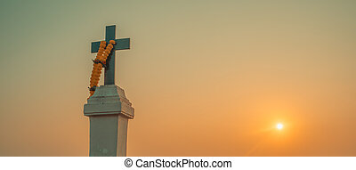 The Christian cross with a floral wreath against the sunset.