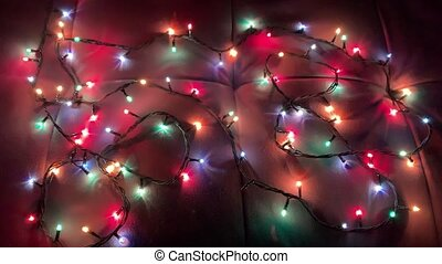The Christmas garland lights up and slowly goes out with multi-colored lights. Stop motion.