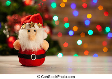 The Christmas toy Santa Claus with three gold stars is in a cap on a light table against the background of the shining multi-colored garland