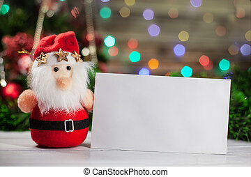The Christmas toy Santa Claus with three gold stars near a white envelope is in a cap on a light table against the background of the shining multi-colored garland