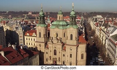 The Church of Saint Nicholas and tiled roofs old town in Prague on a sunny day, Czech Republic.