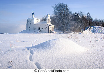 The Church on the hill in the background of a winter landscape.