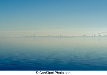 The city in a fog with smoking pipes is reflected in the water against the blue sky