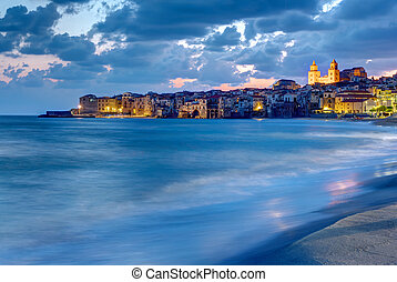 The city of Cefalu and the local beach at dusk