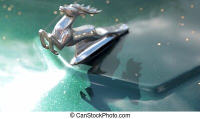 The classic emblem of the Volga GAZ M-21 cars - a figure of a running deer on the hood.