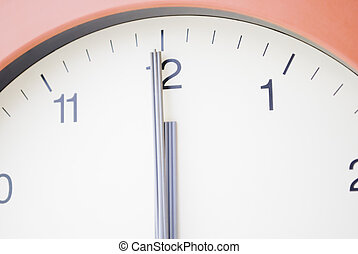 Clock with hands at 12am, midnight. No visible background. Cream face with black markings and sans serif typeface. Grey hands. Terracotta frame.