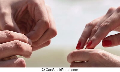 The close-up composition of the newlyweds` hands. The groom is holding the wedding ring in the shell and putting it on the bride`s finger.