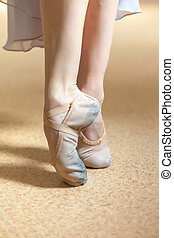 The close-up feet of young ballerina in old pointe shoes