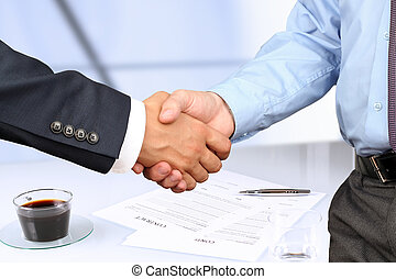 The Close-up image of a firm handshake between two...