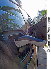 close up of recharging cable and electric car