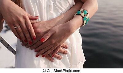 The close-up view of the hands of the man hugging the girl back.