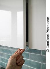 man hand opening or closing kitchen cabinet door
