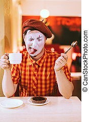 The clown is eating a cake in a cafe and his face is...