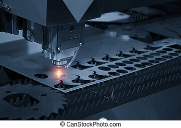 The CNC laser cut machine while cutting the sheet metal with...