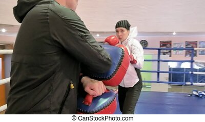 The coach conducts a training battle with paws with a female kickboxer in the ring